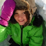 Enfant du village construisant un igloo
